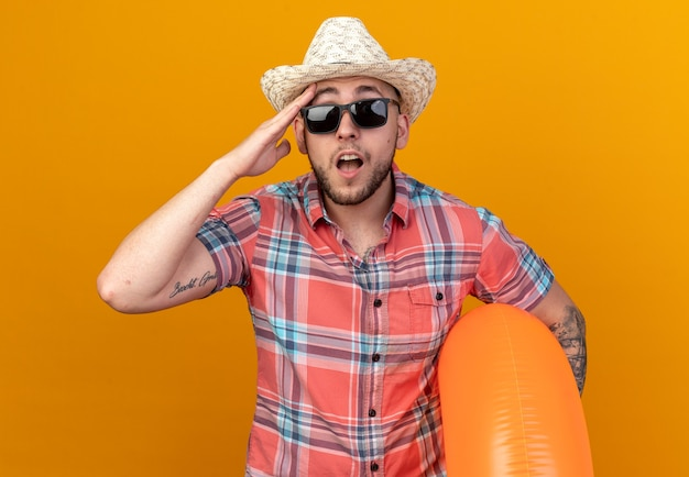 Verrast jonge blanke reiziger man met stro strand hoed in zonnebril hand op het voorhoofd zetten en zwemmen ring geïsoleerd op oranje muur met kopie ruimte houden