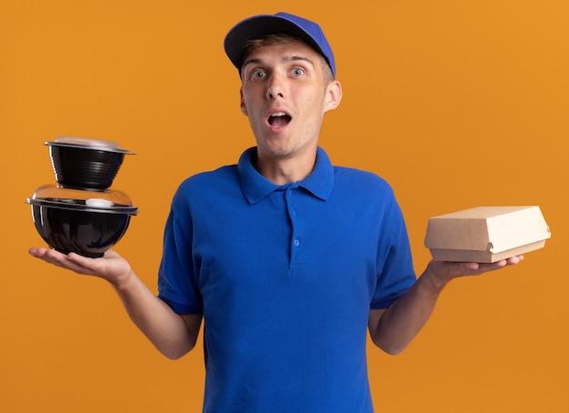 Verrast jonge blonde bezorger houdt voedselcontainers en pakket vast