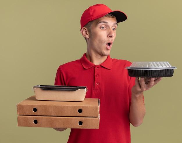 Verrast jonge blonde bezorger houdt voedselpakketten op pizzadozen en kijkt naar voedselcontainer geïsoleerd op olijfgroene muur met kopieerruimte