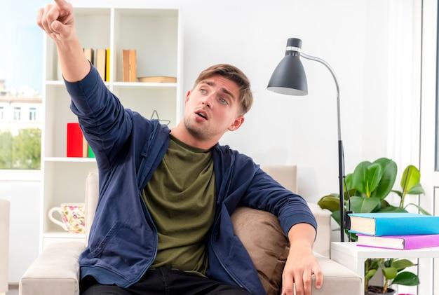 Verrast jonge blonde knappe man zit op fauteuil kijken en wijzen naar kant in de woonkamer
