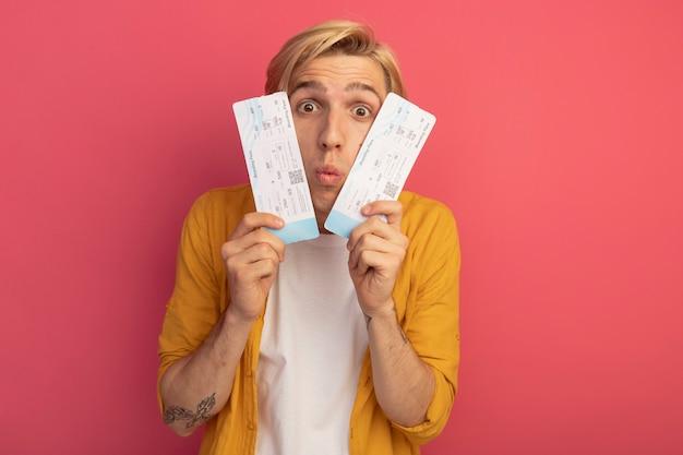 Verrast jonge blonde man met gele t-shirt bedekt gezicht met kaartjes