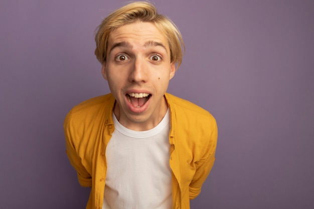 Verrast jonge blonde man met gele t-shirt hand in hand op taille geïsoleerd op paars met kopie ruimte
