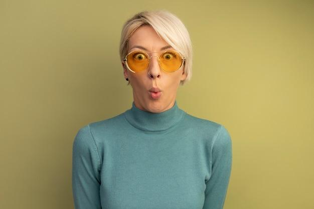 Verrast jonge blonde vrouw die een zonnebril draagt en naar de voorste lippen kijkt die op een olijfgroene muur zijn geïsoleerd