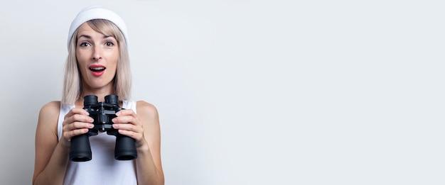 Verrast jonge blonde vrouw met verrekijkers op een lichte achtergrond. banier.