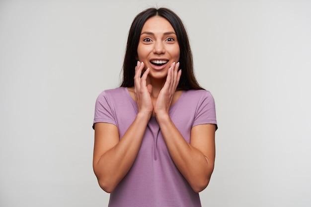 Verrast jonge brunette dame met casual kapsel met grote ogen en mond geopend, handen op haar gezicht te houden terwijl ze op wit staat