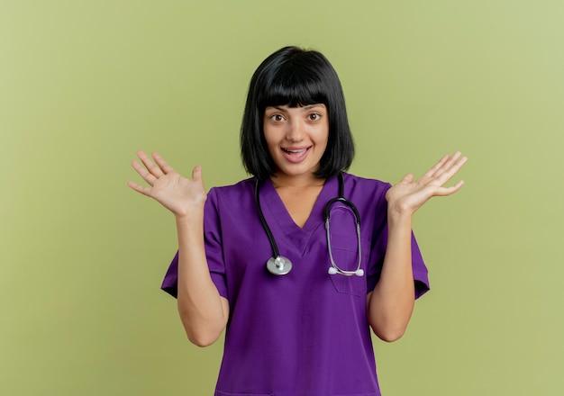 Verrast jonge brunette vrouwelijke arts in uniform met stethoscoop staat met open handen