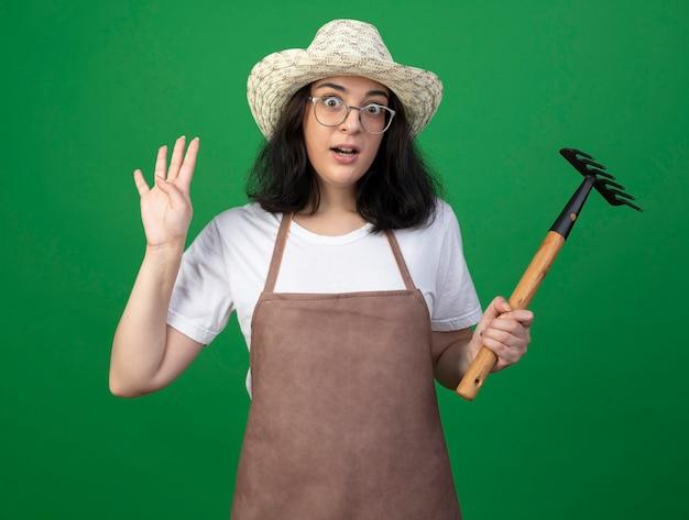 Verrast jonge brunette vrouwelijke tuinman in optische bril en uniform dragen tuinieren hoed houdt hark en gebaren vier met vingers geïsoleerd op groene muur
