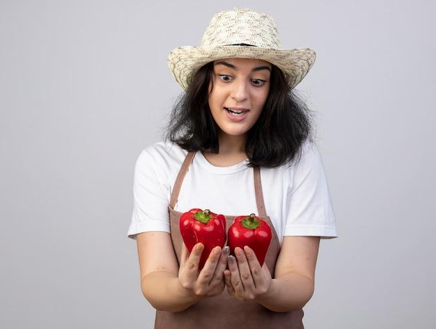 Verrast jonge brunette vrouwelijke tuinman in uniform dragen tuinieren hoed houdt en kijkt naar rode paprika's geïsoleerd op een witte muur met kopie ruimte