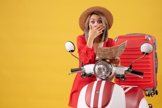 Verrast jonge dame in rode jurk met kaart hand op haar gezicht in de buurt van bromfiets