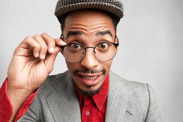 Verrast jonge donkere man met baard en snor, houdt de hand op het frame, draagt een oude modieuze pet en jas,