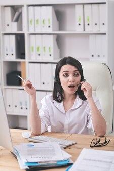 Verrast jonge kantoor vrouw zittend aan tafel met computer en gebaren hand tijdens het gesprek door handsfree apparaat