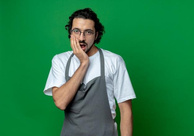 Verrast jonge kaukasische mannelijke kapper bril en golvende haarband dragen uniform hand zetten gezicht geïsoleerd op groene achtergrond met kopie ruimte