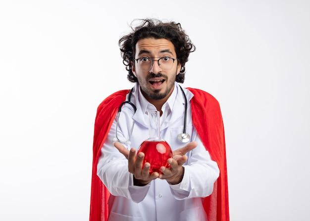 Verrast jonge kaukasische superheld man in optische bril dragen arts uniform met rode mantel en met een stethoscoop om de nek houdt rode chemische vloeistof in glazen kolf
