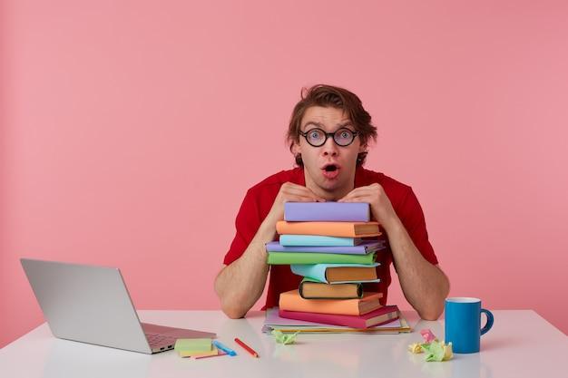 Verrast jonge kerel in glazen, in rood t-shirt, man zit aan de tafel en werkt met laptop en boeken, leunde op een stapel boeken, kijkt geschokt met wijd open mond. geïsoleerd op roze achtergrond.