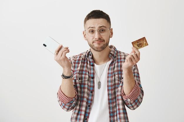 Verrast jonge kerel met een bril poseren met zijn telefoon en kaart