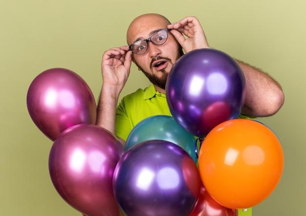Verrast jonge kerel met een geel t-shirt en een bril die achter ballonnen staat