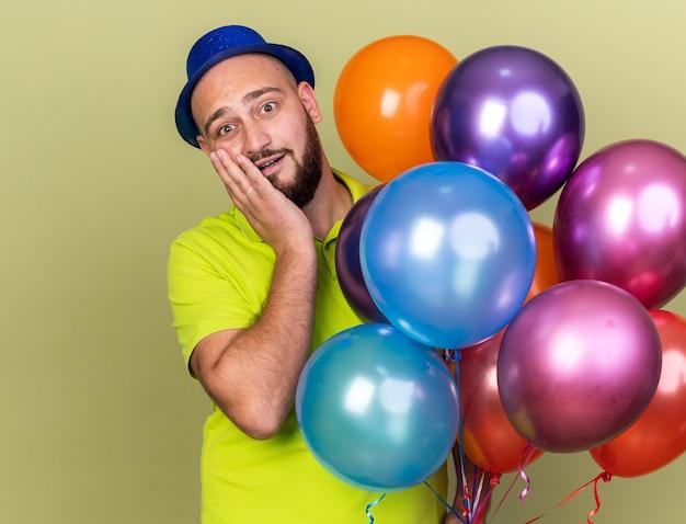Verrast jonge kerel met feestmuts die ballonnen vasthoudt en hand op de wang legt