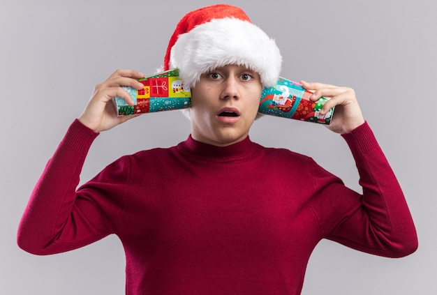 Verrast jonge kerel met kerstmuts met kerst cups op oren geïsoleerd op een witte achtergrond