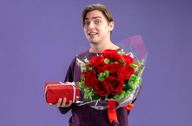 Verrast jonge kerel op valentijnsdag met geschenkdoos met boeket geïsoleerd op blauwe achtergrond