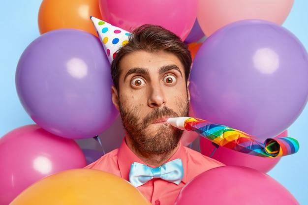Verrast jonge kerel poseren omringd door kleurrijke verjaardagsballons