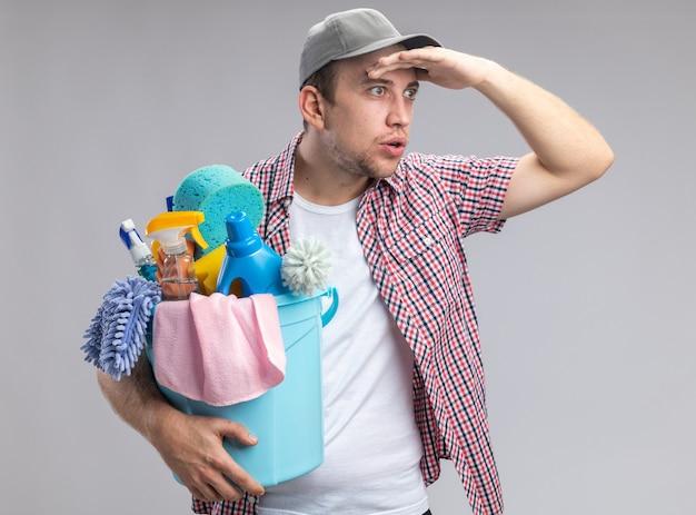 Verrast jonge kerel schoner met pet met emmer met schoonmaakgereedschap kijkend naar afstand met de hand geïsoleerd op een witte muur