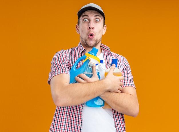 Verrast jonge kerel schoner met pet met schoonmaakmiddelen geïsoleerd op een oranje achtergrond