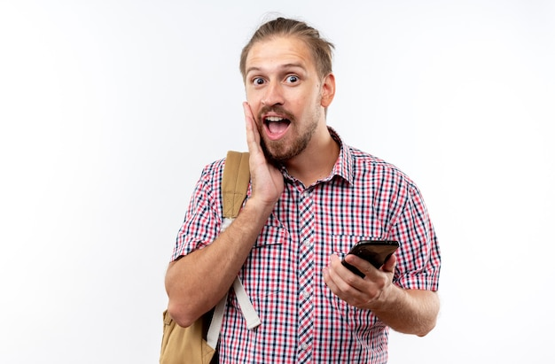 Verrast jonge kerel student dragen rugzak met telefoon hand op de wang geïsoleerd op een witte muur zetten