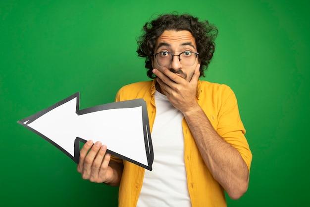 Verrast jonge knappe blanke man met bril houden pijlteken die naar kant kijkt camera houden hand op mond geïsoleerd op groene achtergrond