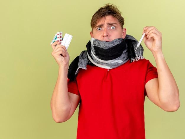 Verrast jonge knappe blonde zieke man met sjaal weergegeven: medische pillen en thermometer kijken naar camera geïsoleerd op olijfgroene achtergrond met kopie ruimte