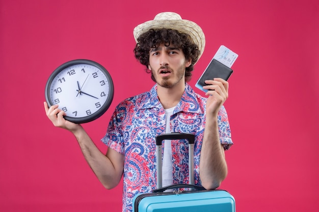 Verrast jonge knappe gekrulde reiziger man met hoed met portemonnee en vliegtuigtickets, klok en arm op koffer op geïsoleerde roze muur met kopie ruimte