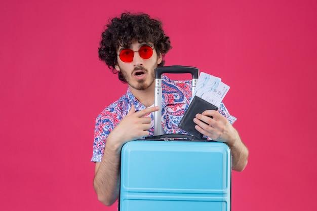 Verrast jonge knappe gekrulde reiziger man met zonnebril met portemonnee en vliegtuigtickets wijzend naar hen met handen op koffer op geïsoleerde roze muur met kopie ruimte