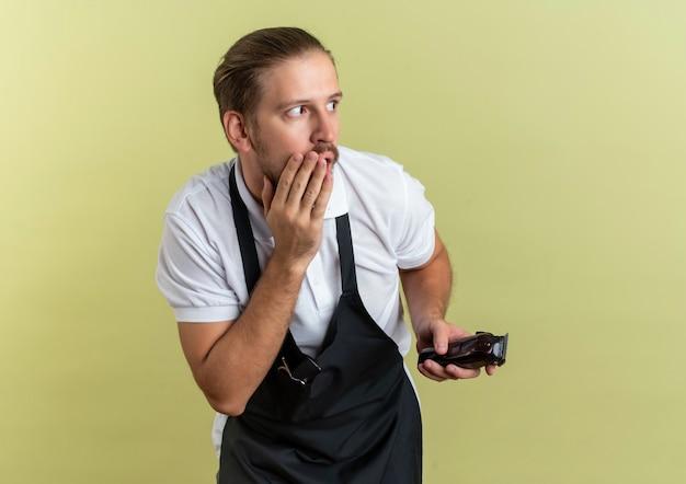 Verrast jonge knappe kapper met tondeuse hand op mond zetten kant geïsoleerd op olijfgroene muur