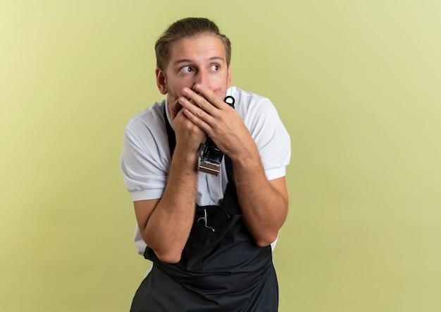 Verrast jonge knappe kapper met tondeuse kijken kant zetten handen op mond geïsoleerd op olijfgroene muur