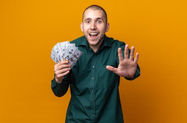 Verrast jonge knappe kerel met een groen shirt met contant geld dat een stopgebaar toont