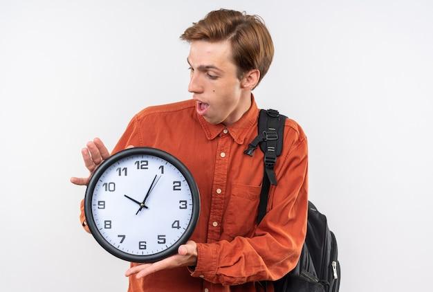Verrast jonge knappe kerel met een rood shirt met rugzak die vasthoudt en kijkt naar de wandklok die op een witte muur is geïsoleerd