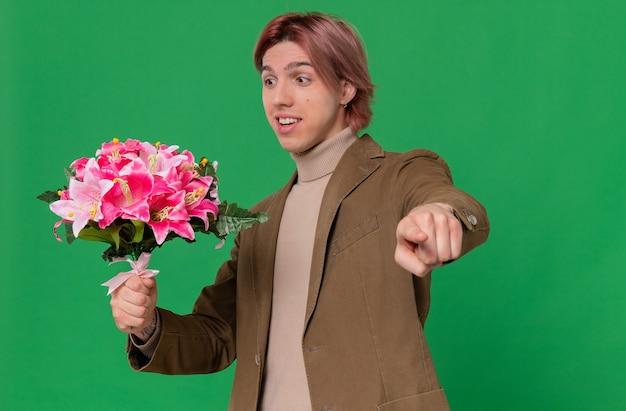 Verrast jonge knappe man die een boeket bloemen vasthoudt en naar voren wijst