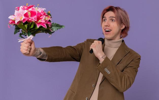 Verrast jonge knappe man met boeket bloemen en microfoon kijkend naar de zijkant