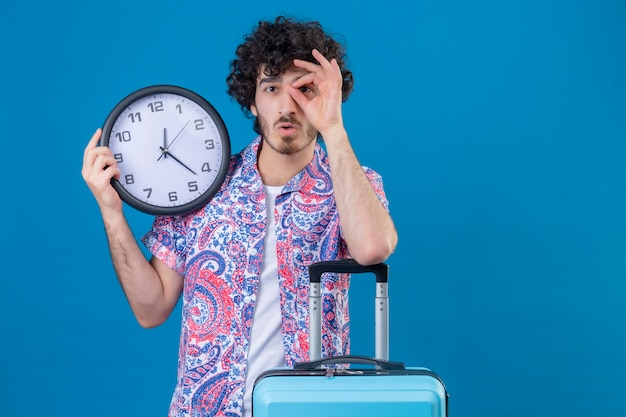 Verrast jonge knappe reiziger man doet blik gebaar met klok met arm op koffer op geïsoleerde blauwe muur met kopie ruimte