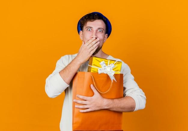 Verrast jonge knappe slavische partij kerel met feestmuts bedrijf geschenkdozen in papieren zak kijken camera hand houden op mond geïsoleerd op een oranje achtergrond met kopie ruimte