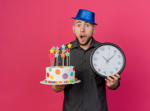 Verrast jonge knappe slavische partij kerel met feestmuts bedrijf verjaardagstaart met sterren en klok kijken camera geïsoleerd op karmozijnrode achtergrond met kopie ruimte