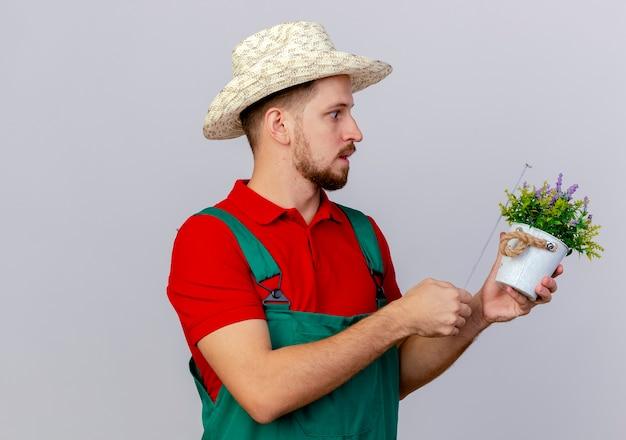 Verrast jonge knappe slavische tuinman in uniform en hoed houden en kijken naar bloempot en meten met tape meter geïsoleerd