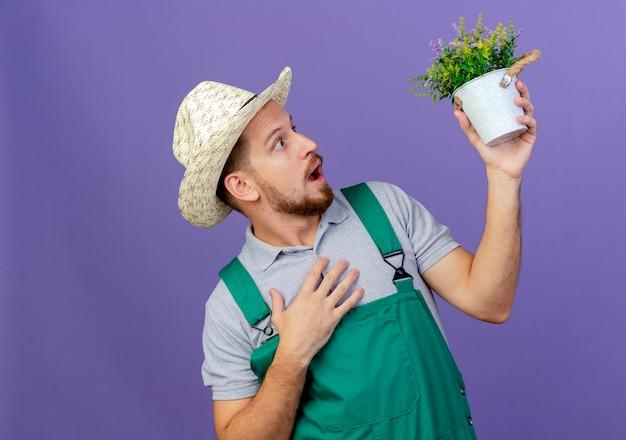 Verrast jonge knappe slavische tuinman in uniform en hoed houden en kijken naar bloempot houden hand op borst geïsoleerd op paarse muur met kopie ruimte