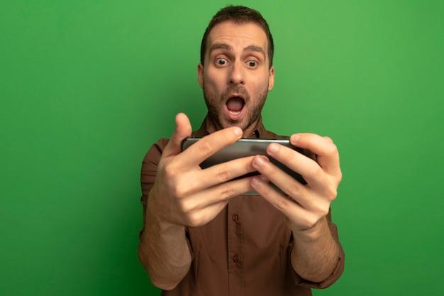 Verrast jonge man houden en kijken naar mobiele telefoon geïsoleerd op groene muur