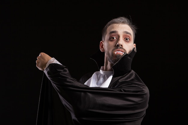 Verrast jonge man in dracula kostuum met grote ogen. man met demon look in halloween kostuum.