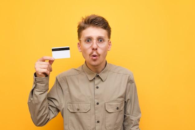 Verrast jonge man in shirt en bril staat op geel met bankkaart in de hand, kijkt in de camera met verbaasd gezicht.