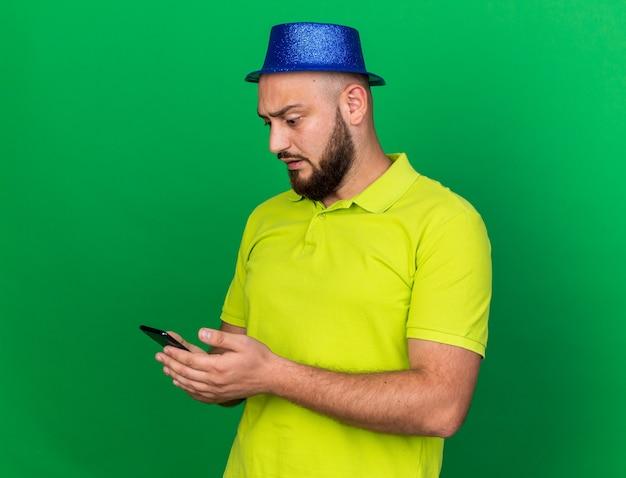 Verrast jonge man met een blauwe feestmuts die de telefoon vasthoudt en bekijkt