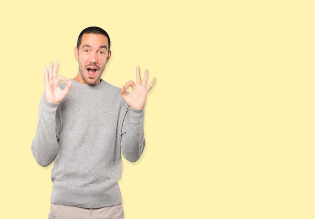 Verrast jonge man met een gebaar van instemming