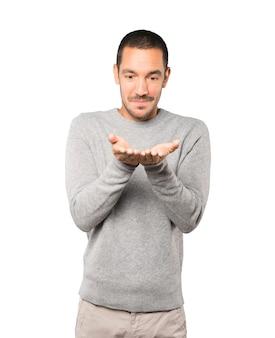 Verrast jonge man met iets met zijn hand