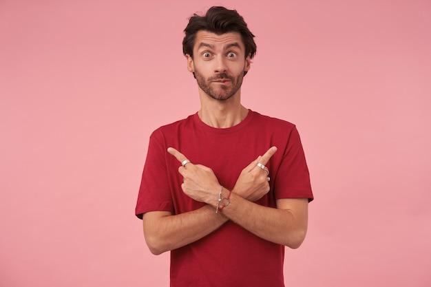 Verrast jonge man met trendy kapsel wijzend met wijsvingers in verschillende richtingen, staande op roze in vrijetijdskleding met opgetrokken wenkbrauwen en bijtende onderlip