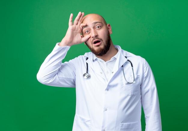 Verrast jonge mannelijke arts medische gewaad en stethoscoop dragen oog openen met hand geïsoleerd op groen